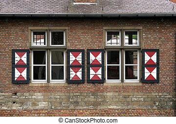 Red brick wall with two windows