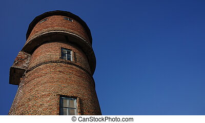 Red brick water tower against blue sky