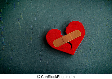 broken heart - red broken heart with a bandage, on textured...