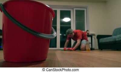 Red bucket and defocused man in red tshirt cleaning up the room. 4K shot