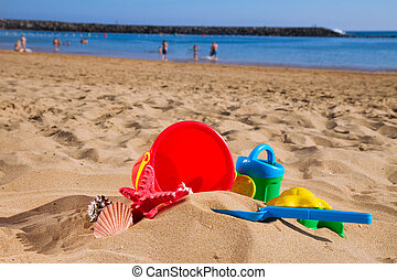 bucket with plastic beach toys in sand on sea shore