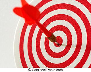 Red bullseye dart arrow hitting target center of dartboard. Concept of success, target, goal, achievement. (selective focus)