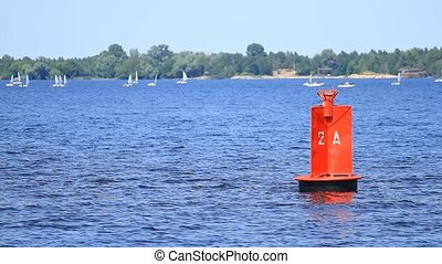 Red buoy and yachts on the river