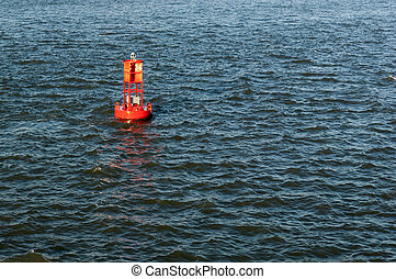 Bright red maritime buoy in the middle of the ocean, surrounded by blue water.