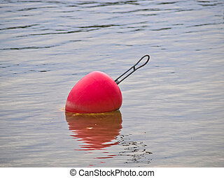 Red buoy dipping in the water, no boat