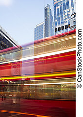Red Bus in motion in City of London on contemporary...