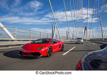 Red cabriolet driving over the bridge