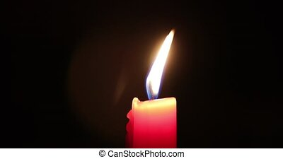 red candle blows off the wind in the dark.
