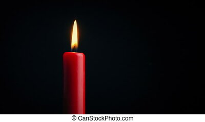 Red Candle Flickers - Closeup shot of a red candle...