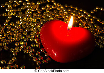 Red candle in the form of heart with a gold beads