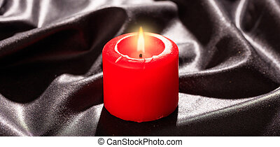 Red candle on black satin background