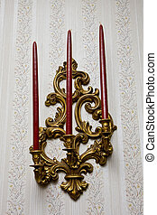 Three red candles in a gold wall sconce on wallpaper