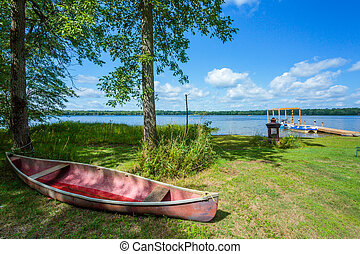Red canoe on a beach of lake.