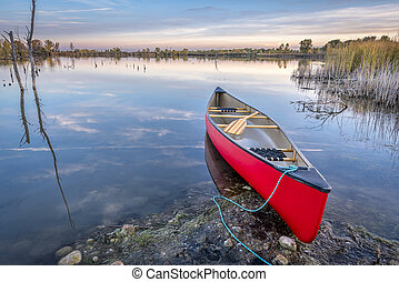 red canoe on a lake shore