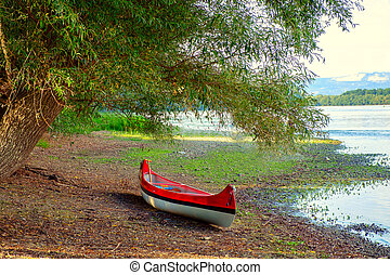Red canoe on beach at river Danube
