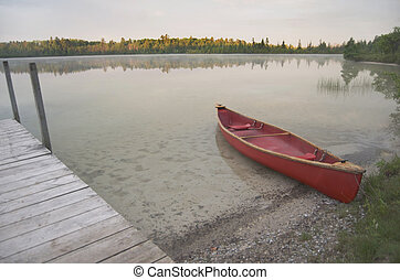 Red Canoe On Calm Lake