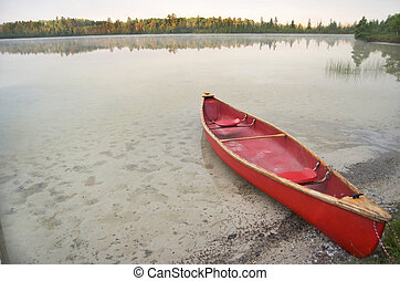 Red Canoe On Calm Lake - Red canoe at the edge of a calm...