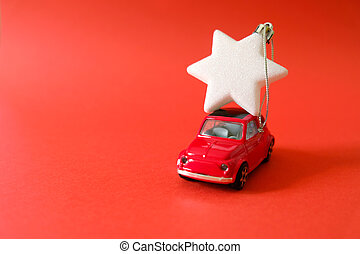 Red car carries a Christmas tree toy, a symbol of the new year