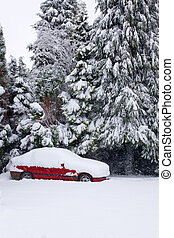 Red car covered in snow - An abandoned red car covered in...