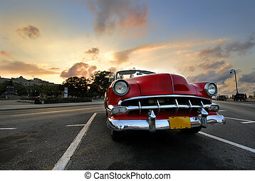 Red car in Havana sunset - View of red classic vintage...