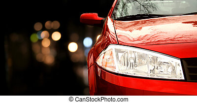 Red car in traffic at night