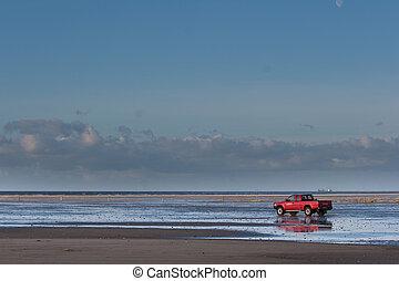 Red car on the beach Island of Fanoe in Denmark