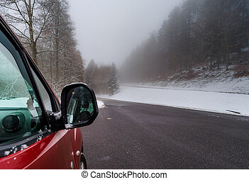 Red car on the winter road in the mountains, forest with snow