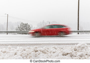 Red car, station wagon driving fast on the road in winter landscape, with snowy weather. Motion blur