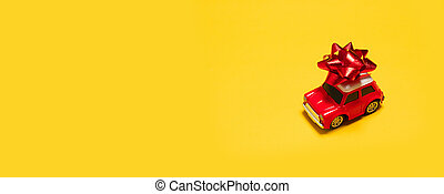 Red car toy with bow on yellow background