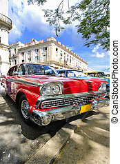 Red car under tree branches in havana, cuba - Old red car...