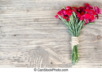 red carnation over wooden table with copy space