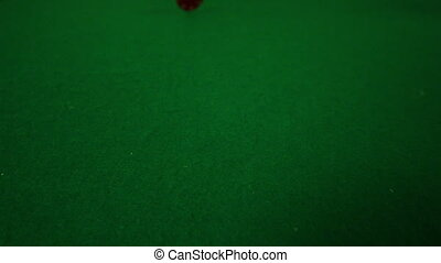 Red casino chip falling towards camera in slow motion