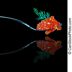 Red caviar on a metal fork isolated on black background