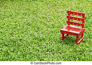 Red chair on green grass texture