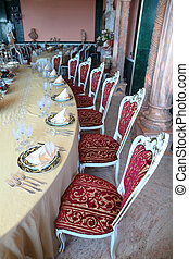 Red chairs and big dinner table with empty dishes: plates...