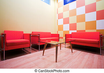 Red chairs and table in waiting room
