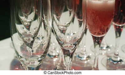 Red champagne pouring in a glass