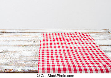 red checkered tablecloth on a wooden kitchen table, copy space