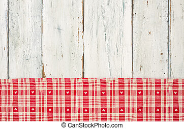 Red checkered tablecloth with hearts on a white wooden backgroun