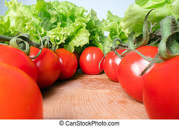 Red cheery tomatoes with lettuce leafs on top of wooden table background. Home grown vegetables, healthy eating lifestyle