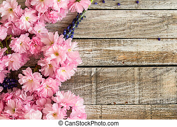 Red cherry blossom with grape hyacinth on white wood texture