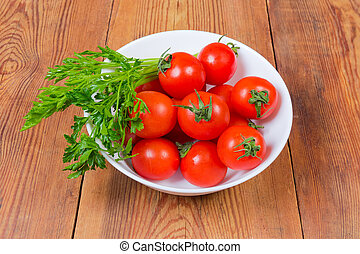 Red cherry tomatoes and parsley in bowl on rustic table