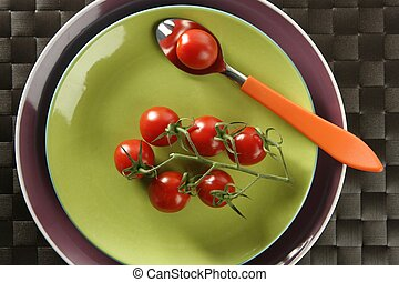 Red cherry tomatoes branch, spoon and green dish