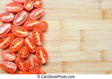 Red cherry tomatoes chopped on a wooden cutting board