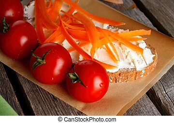 Red cherry tomatoes in front of bread with cottage