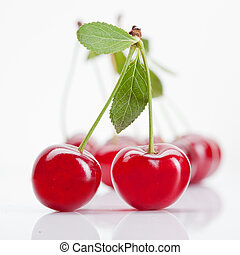 Red cherry with leaves isolated on white