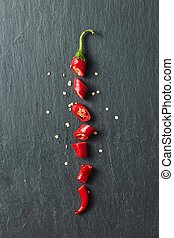 Red chili pepper cut into slices isolated on black stone...