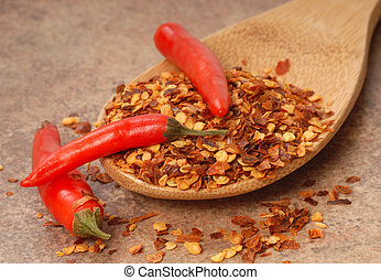 Hot red chili peppers and red pepper flakes on a wooden spoon