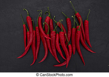 red chili peppers on black slate