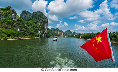Red Chinese national flag on a boat sailing on Li River